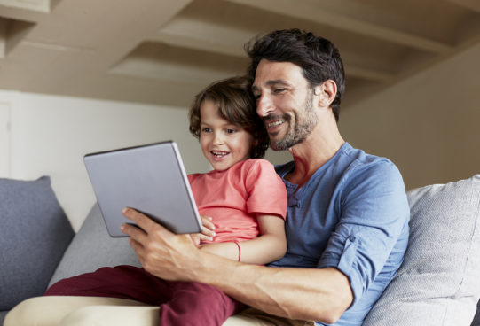 Happy father and son using digital tablet on sofa at home