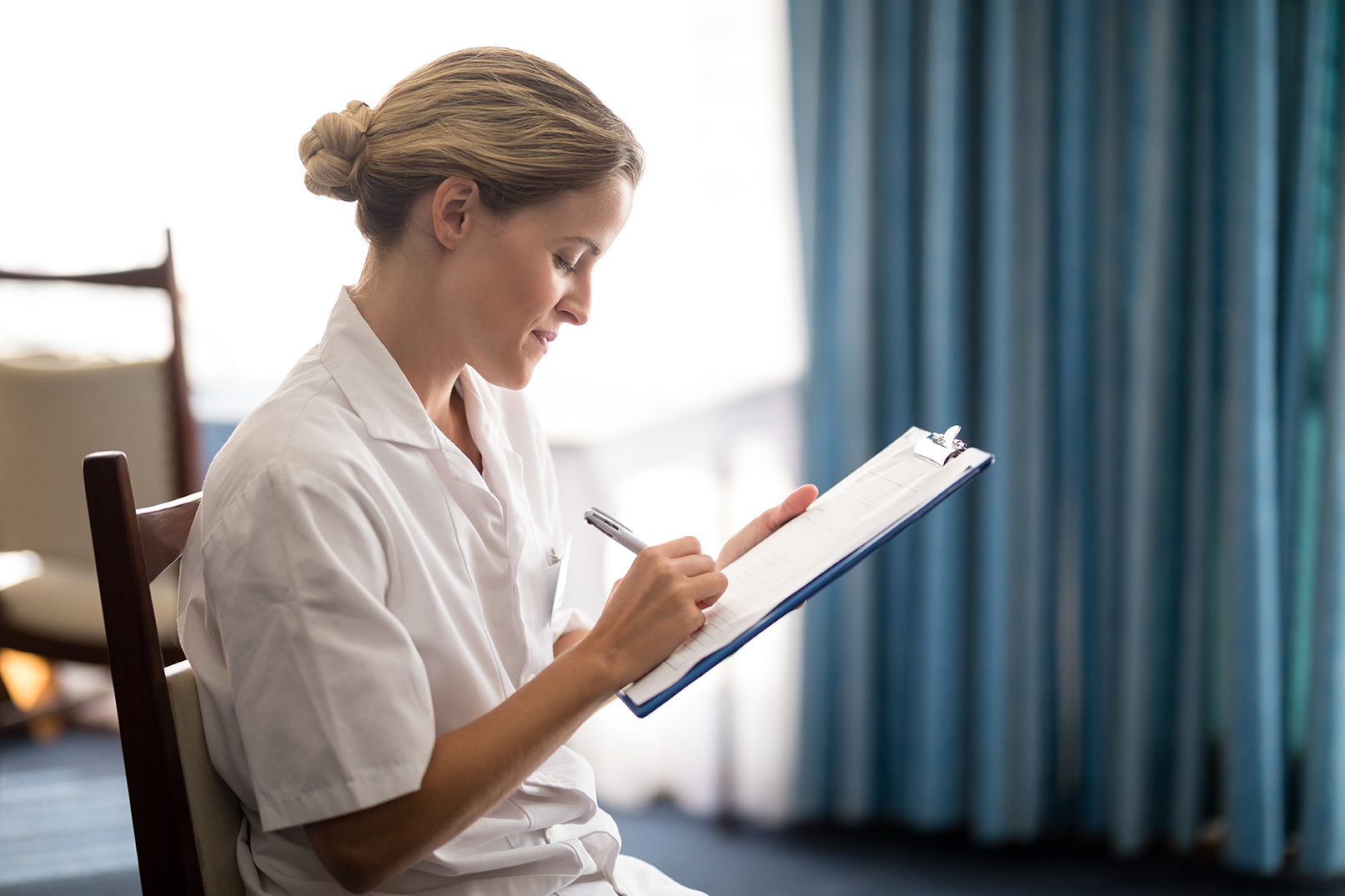 Side view of young female doctor writing on clipboard at retirement home